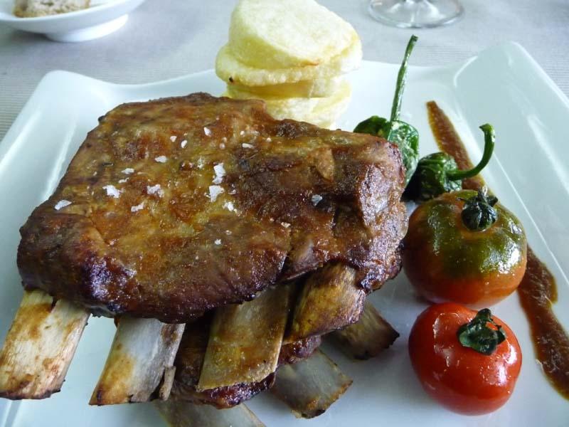 Costilla de Duroc a la parrilla con patata frita gallega, pimientos de Padrón y tomate.